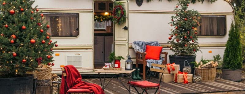 Caravan mobile home with terrace, Mobile home decorated with Christmas decor. Festive atmosphere - lights, red blankets, Christmas trees. Waiting for the snow. Caravan camping. mobile home trailer.